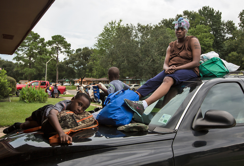 Adrianna Norwood and her two sons sit on her destroyed car in front of the flooded home she rents, with nowhere to go. The main shelters turned them away because they were full, so they slept in a different church every night until her son who has epilepsy had two convulsions. Only then was the family taken in at the Medical Special Needs Shelter at the LSU where her son could get medical help