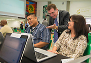 Houston ISD Superintendent Dr. Terry Grier, center, checks out new laptops given to Roderick Bodeta, left, and Judith Casupang, right, during the PowerUp laptop distribution and training at Austin High School, August 13, 2013.