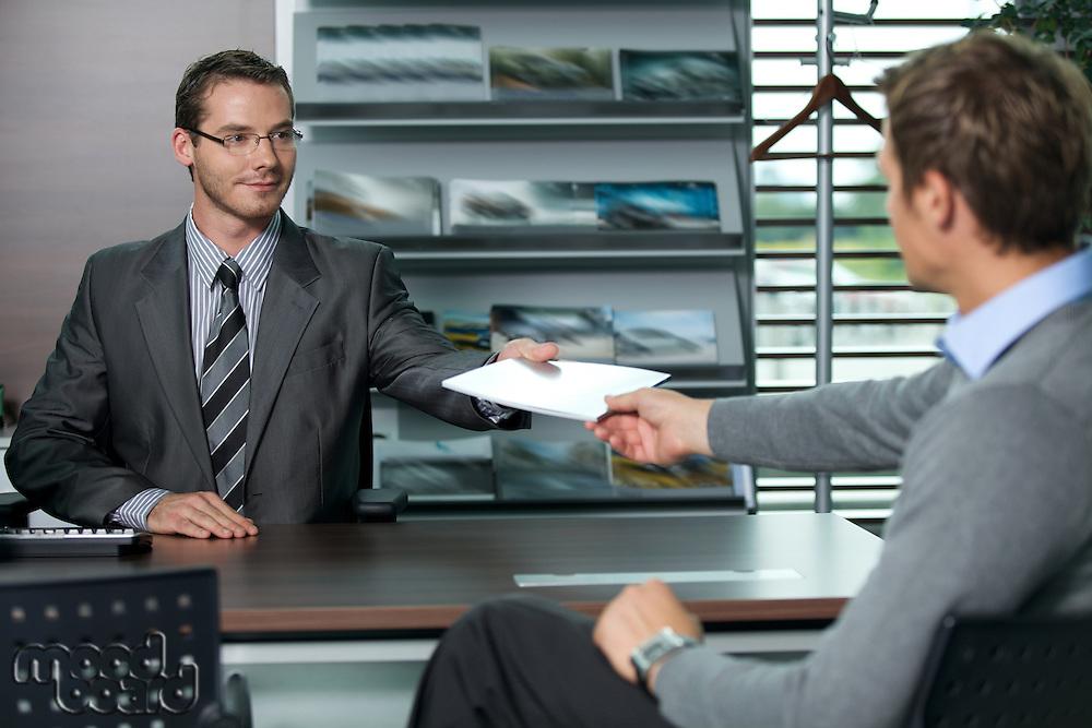 Car salesperson giving catalog to businessman