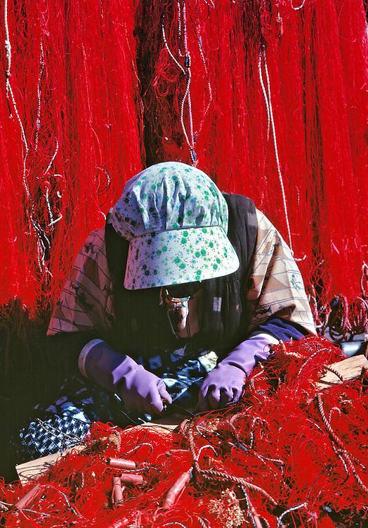 A net mender critically checks fishing nets for holes at Nikiri, Ago Bay, Honshu, Japan.