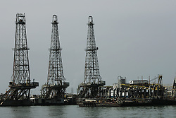 """A drilling rig used to create new wells waits in a port to be taken out to sea.  Since the removal of nearly 18,000 workers after an oil strike in Venezuela in 2002, PDVSA, the state run oil company has gone through drastic changes.  Struggling to replace the dismissed workers and return production to pre-strike quantities, PDVSA has also undertaken the financing and coordination of huge social programs.  PDVSA has invested billions of dollars in various education, food, medicine and infrastructure projects, calling itself the """"new"""" PDVSA."""