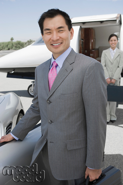 Portrait of mid-adult businessman standing in front of convertible, mid-adult businesswoman in background.