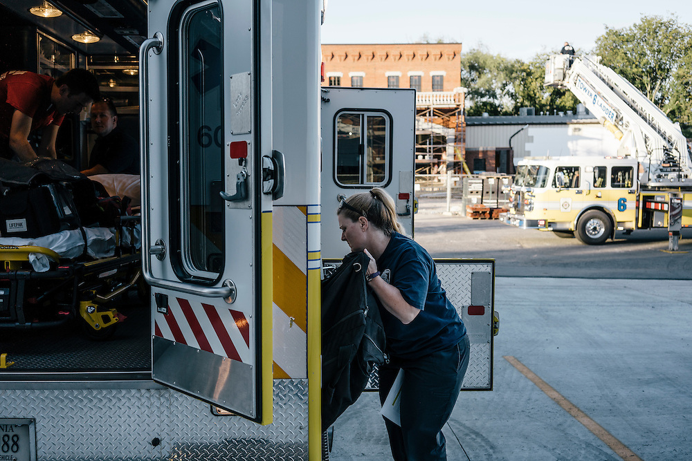 Heidi Wallner, firefighter, National Registry emergency medical technician, and safety supervisior for LSG Sky Chefs, loads equipment onto the ambulance at Station 6 in Ashburn Virginia on Sept. 23, 2015. Wallner is a volunteer, working one night a week with other EMTs.
