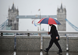 © Licensed to London News Pictures. 29/08/2012. London,UK. People with umbrellas walk along London Bridge in the rain in Central London today 29th August 2012 .Photo credit : Thomas Campean/LNP.