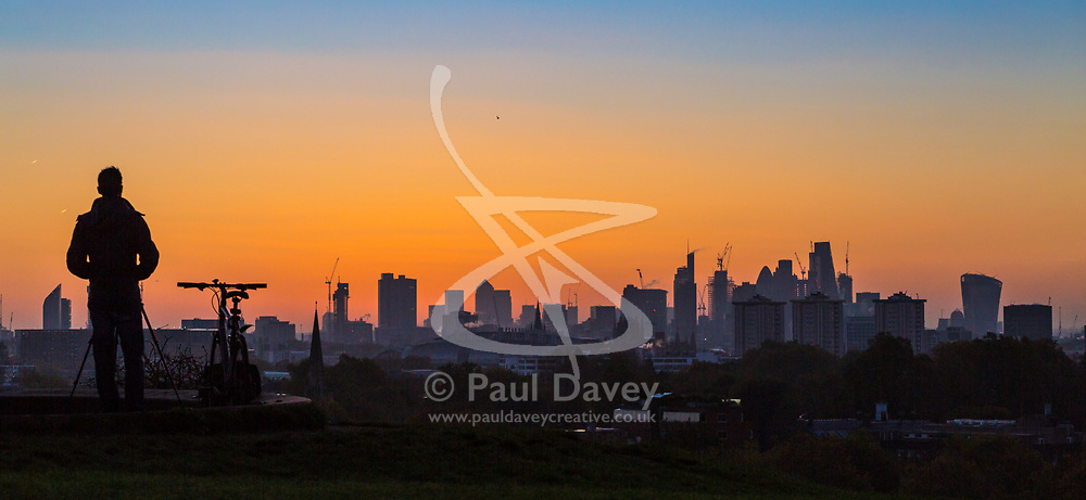 London, October 27 2017. A photographer waits for the sun to appear behind the skyscrapers as the day breaks over London, seen from Primrose Hill. © Paul Davey