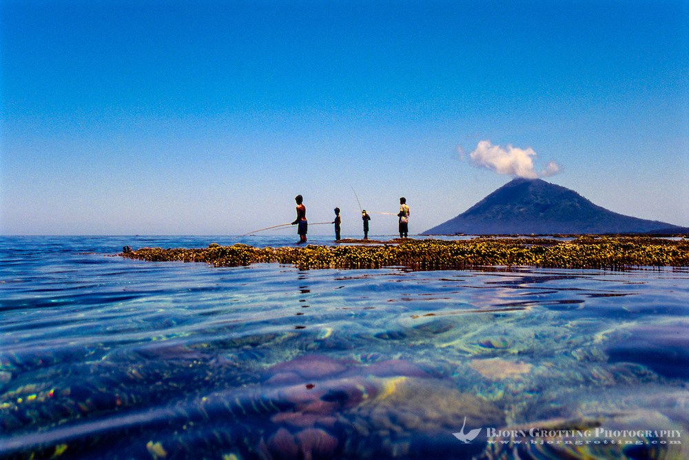 Indonesia, Sulawesi, Bunaken. Children fishing on the reef with Manado Tua in the background.