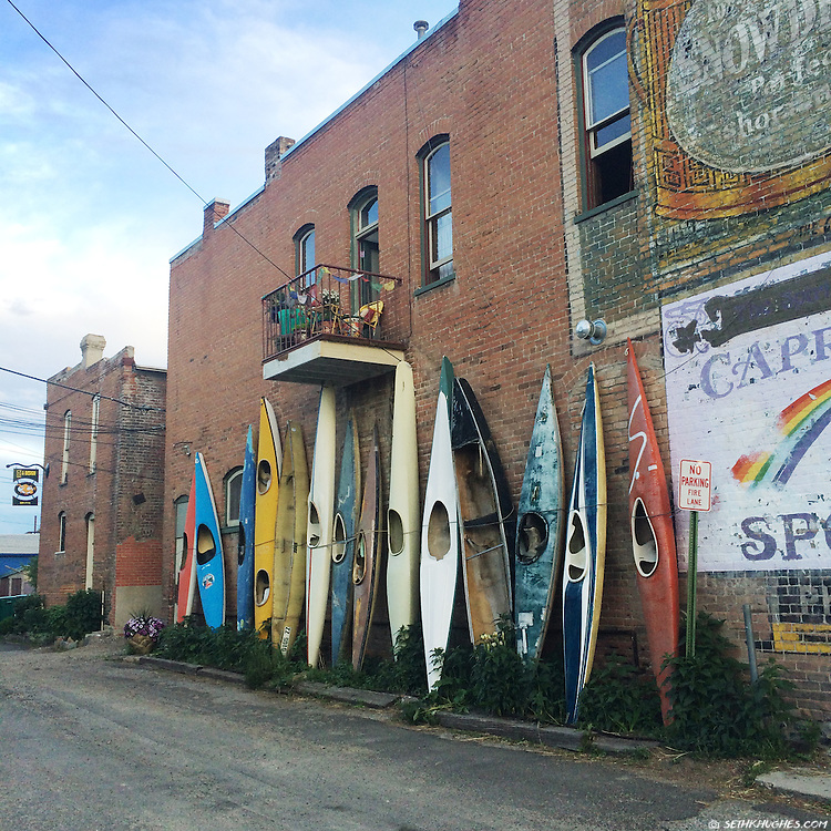 A row of vintage kayaks decorate an alleyway in downtown Salida, Colorado.