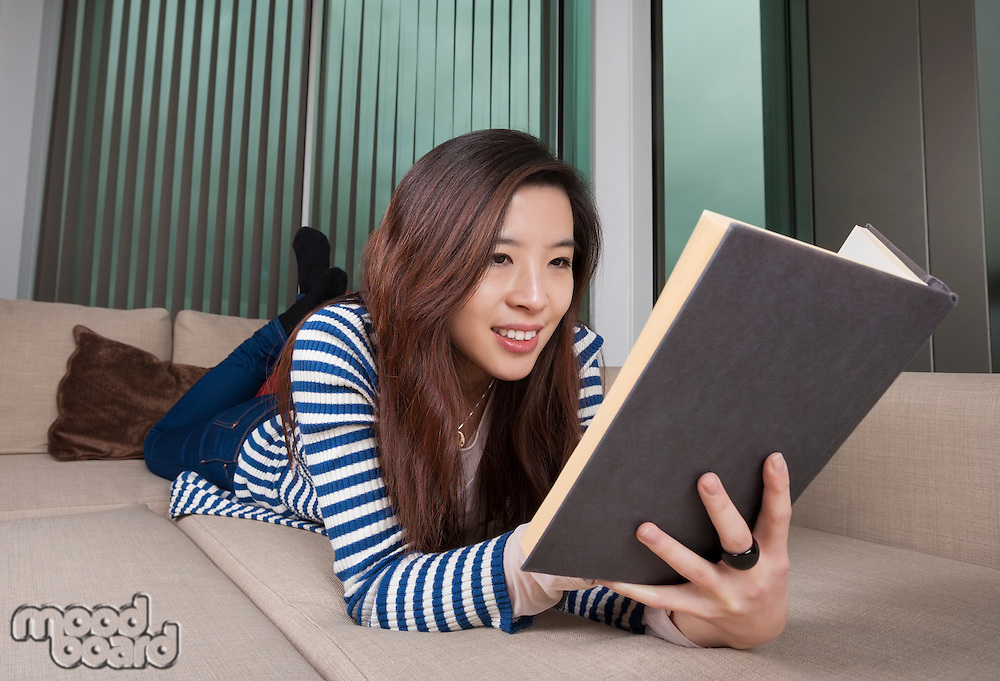 Relaxed young woman reading book at home
