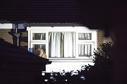 © Licensed to London News Pictures . 25/07/2017 . Oldham , UK . A window is lit up from outside by what is believed to be a police searchlight , at the scene where an armed siege that began at 3.15am on Tuesday 25th July in a house on Pemberton Way in Shaw , is ongoing in to a second night . A man named locally as Marc Schofield is reported to be holding a woman hostage after earlier releasing two children . The gas supply in the area has been cut off and several neighbouring properties have been evacuated . Photo credit : Joel Goodman/LNP