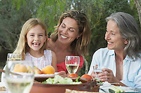 Grandma mother and daughter (5-6) sitting at table in garden girl laughing