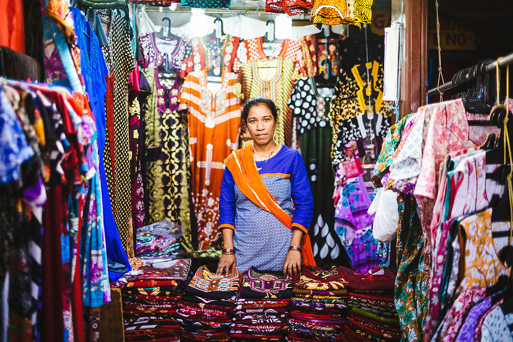 A woman poses for a portrait at her small shop selling women's clothing at the Margao market.