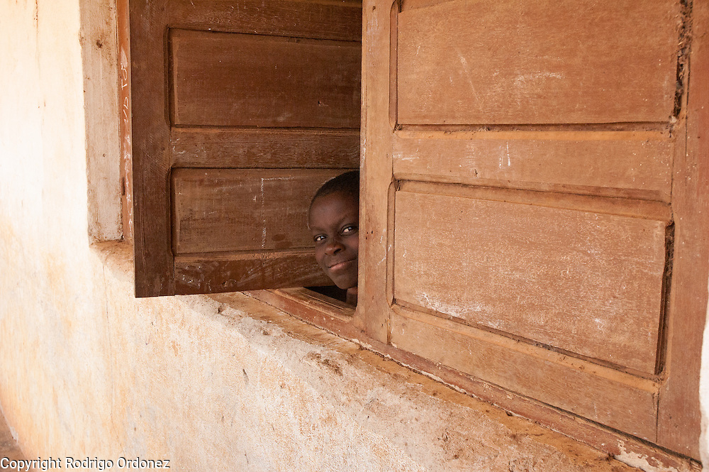 A girl peeks out of the window of a classroom.<br /> Save the Children distributed education kits to students at Groupe Scolaire Quartier Lyc&eacute;e in Man, western C&ocirc;te d'Ivoire. Children received a backpack with school supplies such as pens, pencils, sharpeners, notebooks, rulers, a pair of compasses and a portable chalkboard.