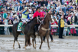 Always Dreaming with John R. Velazquez up, left is led to the winner circle by lead outrider Greg Blasi after winning the 143rd running of the Kentucky Derby at Churchill Downs May 6, 2017.