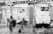 Panama Canal Employees walking next to the Miraflores Locks locomotives.