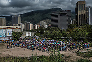 CARACAS, VENEZUELA – JANUARY 15, 2015: Hundreds of people waited in line for hours to enter a state-run supermarket to purchase price-controlled food.  Despite being a petro-state with one of the largest oil reserves in the world, basic food goods such as cooking oil, milk, chicken, coffee, rice, sugar and corn meal are scarce in Venezuela. People must wait in grueling long lines to buy small amounts of affordable food. The suffering of Venezuelan families is expected to worsen next year. Beyond the I.M.F.'s warning that inflation could surpass 2,300 percent, observers worry that the leftist government will continue to refuse international aid for political reasons.