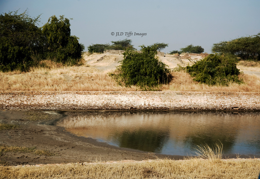 Lothal Harappan city mound, partly excavated, seen from across its water tank.