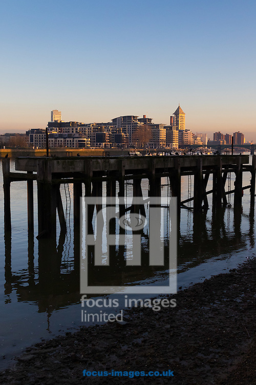 The sun illuminates the apartment blocks of Imperial Wharf as an old dock's pilings are reflected in the outgoing tide of the River Thames, London <br /> Picture by Paul Davey/Focus Images Ltd +447966 016296<br /> 24/02/2016