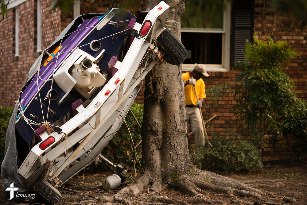 A man cleans up next to a toppled boat in the front yard of a home damaged by flooding on Thursday, Oct. 8, 2015, in Columbia, S.C. LCMS Communications/Erik M. Lunsford