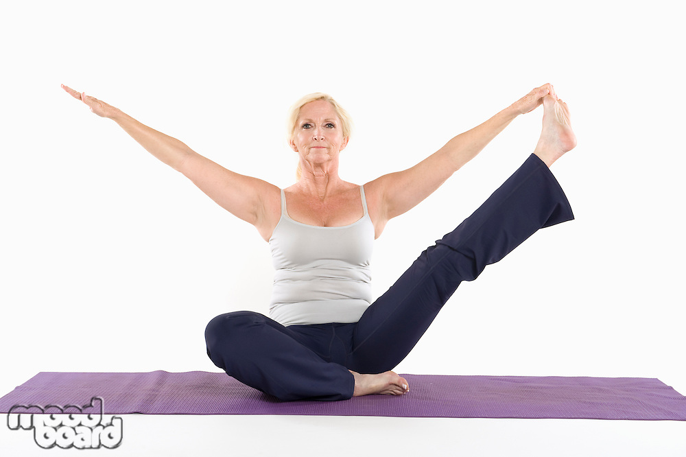 Mature woman sitting on mat and doing yoga with arms outstretched