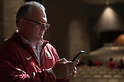 Marc Smith, father of Flower Mound Marcus High School senior tight end Kaden Smith, texts a photo of his son after he signed his National Letter of Intent to play football at Stanford University during his high school signing day on February 3, 2016. (Cooper Neill for The New York Times)