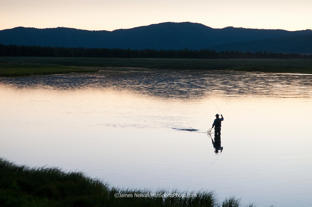 An angler brings a trout to the net on the Henry's Fork (a.k.a., North Fork) of the Snake River near Island Park, Idaho.