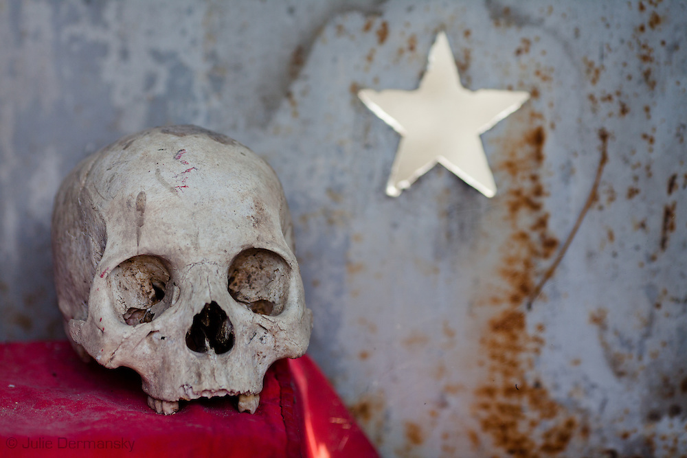 Shrine inside in the tomb  Francois Michel practices voodoo in the National Cemetery in Port-au-Prince. The National Cemetery in Haiti is the base for voodoo priests.<br /> Haitian Voodoo is a syncretic religion that originates in  Haiti based upon a merging of the beliefs and practices of West African peoples with Arawakian religious beliefs, and Roman Catholic Christianity.