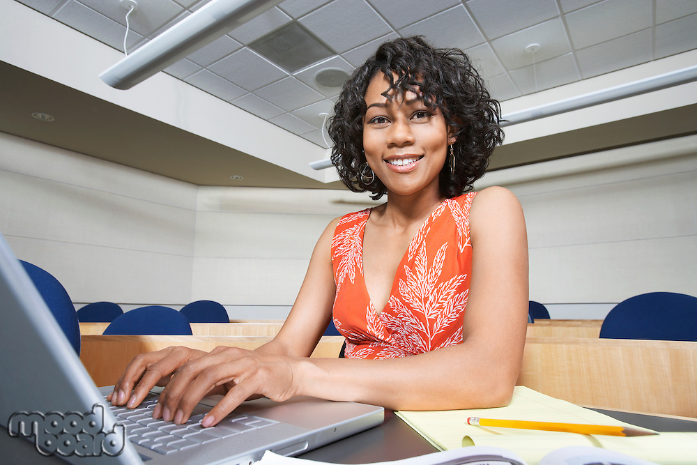 Female student using laptop in lecture theatre, portrait