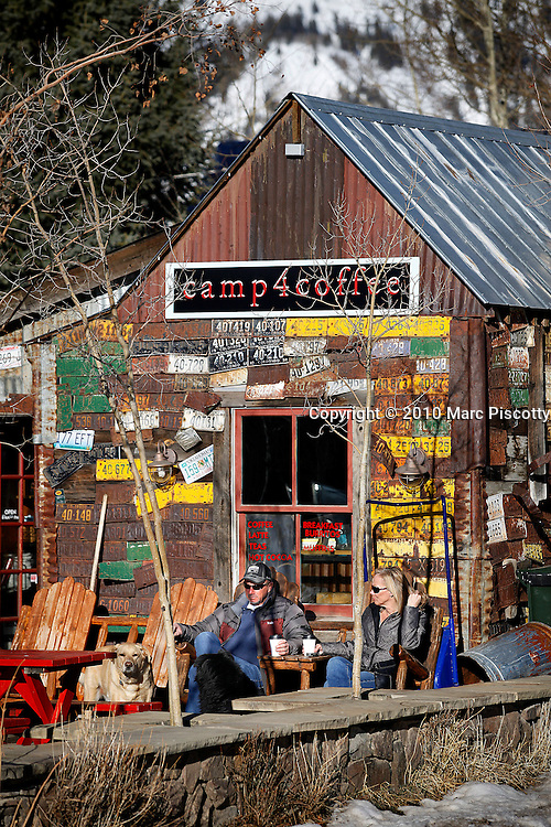 "SHOT 3/16/10 5:35:38 PM - A couple with their dog enjoy an afternoon coffee and chat outside of Camp 4 Coffee in Crested Butte, Co. The beloved local roaster pours scruffy mountaineers their morning cup in a former coal shed plastered with vintage license plates. Crested Butte is a Home Rule Municipality in Gunnison County, Colorado, United States. A former coal mining town now called ""the last great Colorado ski town"", Crested Butte is a destination for skiing, mountain biking, and a variety of other outdoor activities. .(Photo by Marc Piscotty / © 2010)"