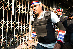 © Licensed to London News Pictures. 17/01/2014. Anti-Government protestors search an abandoned apartment complex looking for a suspect who threw an explosive device injuring eight people during an anti-government street rally on January 17, 2014 in Bangkok, Thailand. Anti-government protesters launch 'Bangkok Shutdown', blocking major intersections in the heart of the capital, as part of their bid to oust the government of Prime Minister Yingluck Shinawatra ahead of elections scheduled to take place on February 2. Photo credit : Asanka Brendon Ratnayake/LNP