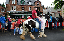 © Licensed to London News Pictures. <br /> 05/06/2014. <br /> <br /> Appleby, Cumbria, England<br /> <br /> A young couple ride their horse along the pavement as gypsies and travellers gather during the annual horse fair on 5 June, 2014 in Appleby, Cumbria. The event remains one of the largest and oldest events in Europe and gives the opportunity for travelling communities to meet friends, celebrate their music, folklore and to buy and sell horses.<br /> <br /> The event has existed under the protection of a charter granted by King James II in 1685 and it remains the most important event in the gypsy and traveller calendar.<br /> <br /> Photo credit : Ian Forsyth/LNP