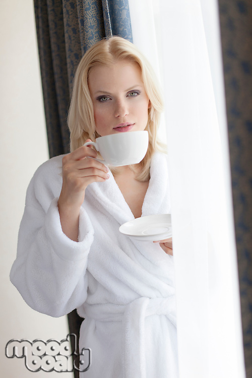 Portrait of beautiful young woman in bathrobe drinking coffee at hotel room