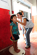 A young girl from the community of Ciudad Romero, having her height measured as part of a series of medical investigations carried out by the 'Nefrolempa' health team into the high incidence of chronic renal failure in the region.<br /> <br /> Ciudad Romero, Bajo Lempa, El Salvador. 2011.<br /> The 'Nefrolempa' research project is a collaboration between the El Salvador Ministry of Health, the Nephrology Institute of Cuba's Ministry for Public Health and the United Bajo Lempa Committee Association. The aim of the project is to investigate the reasons for the high levels of Chronic Kidney Disease (CKD) suffered by the communities within the Bajo Lempa region. It is exploring whether the use of agrochemicals might be a factor in the prevalence of the disease.<br /> <br /> Medical team: Dr Elsy Brizuela de Jimenez, Directora Unidad de Salud. Miriam Colindres, Nurse. Maria Eraida Velasquez, clinic and laboratory worker. Ecuilia Castro Peraza, Nutritionist. Veronica Contreras, Education for health. Guadelupe Nunez, Psychologist. Luis Diaz General support worker. Dr Raul Herrera Valdes, Nefrologo, Cuba. Dr Miguel Almaguer Lopez, Nefrologo Cuba. Dr Carlos Orantes, Salvadorean Nefrologist. Dr Juan Carlos Awaya, Salvadorean Nefrologist.