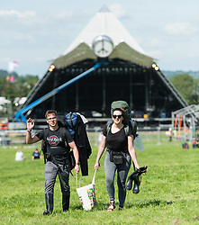 © Licensed to London News Pictures. 24/06/2015. Pilton, UK.   Festival goers walk past the Pyramid Stage at Glastonbury Festival as they find a good area set up their tents shortly after entering the site at 8am on  Wednesday Day 1 of the festival.        The pedestrian gates to the festival opened at 8am this morning, with many festival goers arriving and waiting throughout last night for the opening.  This years headline acts include Kanye West, The Who and Florence and the Machine, the latter having been upgraded in the bill to replace original headline act Foo Fighters.  Photo credit: Richard Isaac/LNP