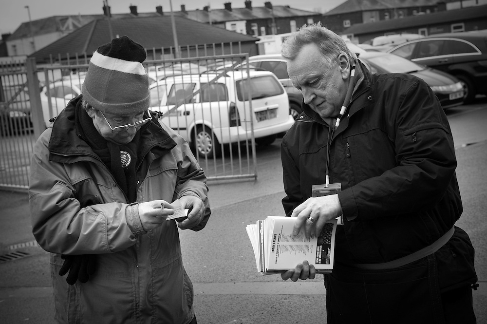 FC United of Manchester play a local team Chorley at Bury football club's ground in Lancashire, Britain. Volunteers sell programs outside the ground before the start of the match.