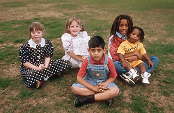 Multiracial group of children sitting on grass,