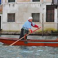 """VENICE, ITALY - JANUARY 06:  One of the rowers dressed in costume heads towards the start line few minutes ahead of the """"Befana"""" Regatta on January 6, 2014 in Venice, Italy. In Italian folklore, Befana is an old woman who delivers gifts to children throughout Italy on the feast of the Epiphany on January 6 in a similar way to Saint Nicholas or Santa Claus.  (Photo by Marco Secchi/Getty Images)"""