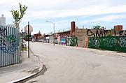 Deserted empty, dangerous, urban street in industrial neighborhood, Bushwick, Brooklyn, New York City.