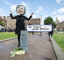 © Licensed to London News Pictures. 09/06/2017. London, UK. A campaigner from the organisation Avaaz wears a Theresa May head as she mourns the 'death of hard Brexit' outside Parliament. Prime Minister Theresa May failed to secure a parliamentary majority in the 8 June 2017 General Election, which she claimed was needed for effective negotiations for Britain's exit from the European Union.  Photo credit: Rob Pinney/LNP