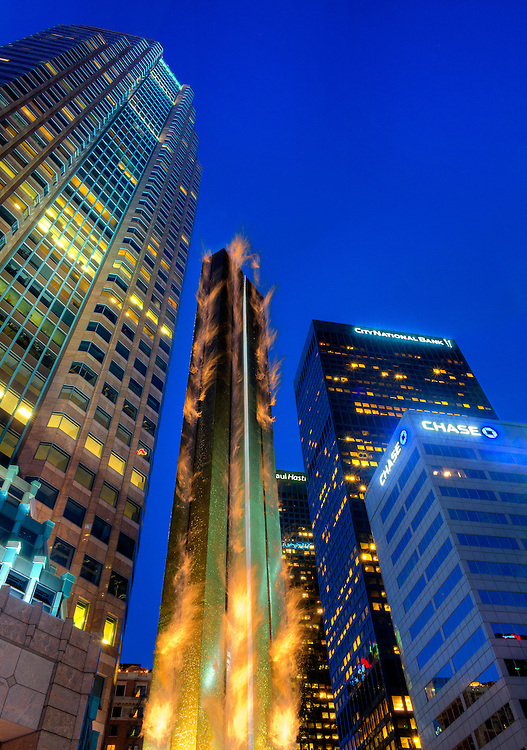 Dramatic evening view of 30 foot tall Bronze water and fire sculpture. Sculpture is surrounded by tall glass and steel skyscrapers and flames are shooting from sculpture. Located at corner of  Wilshire Blvd. and figueroa  downtown Los Angeles