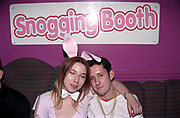 A girl dressed as a playboy bunny with her arm around a man in a snogging booth, Garlands, Liverpool, UK, 2002