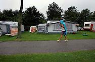 THE NETHERLANDS-LEIDSCHENDAM- Rainy vacation. Foto: Gerrit de Heus. Leidschendam. 04/07/05. Kamperen in eigen land is niet altijd leuk, deze campinggast op camping Vlietland in Leidschendam probeert droog te blijven opweg naar de douche.