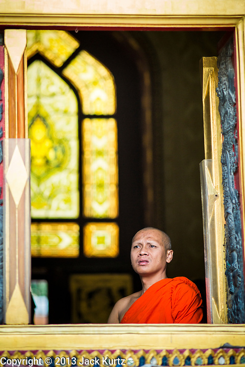 """25 FEBRUARY 2013 - BANGKOK, THAILAND: A Buddhist monk looks out a window at Wat Benchamabophit Dusitvanaram (popularly known as either Wat Bencha or the Marble Temple) on Makha Bucha Day. Makha Bucha is a Buddhist holiday celebrated in Myanmar (Burma), Thailand, Cambodia and Laos on the full moon day of the third lunar month (February 25 in 2013). The third lunar month is known in Thai is Makha. Bucha is a Thai word meaning """"to venerate"""" or """"to honor"""". Makha Bucha Day is for the veneration of Buddha and his teachings on the full moon day of the third lunar month. Makha Bucha Day marks the day that 1,250 Arahata spontaneously came to see the Buddha. The Buddha in turn laid down the principles his teachings. In Thailand, this teaching has been dubbed the 'Heart of Buddhism'.      PHOTO BY JACK KURTZ"""