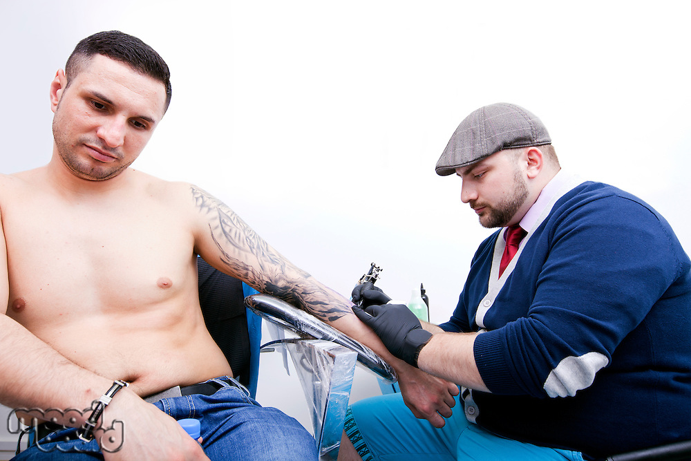 Shirtless young man getting tattoo on arm in parlor
