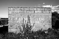 Reportage sul comune di Alessano per il progetto propugliaphoto..Edificio rurale utilizzato per deposito agricolo..Macurano è un villaggio rupestre considerato un luogo di scambio e commercio, simbolo della cultura dell'olio per la presenza ad oggi di alcune tracce nelle grotte e di frantoi funzionanti nella zona. L'insediamento è caratterizzato da una serie di grotte sia naturali che scavate nel calcare, cisterne per la raccolta dell'acqua, sistemi di canalizzazione che scendono da Montesardo, viottoli, scalette e vie più larghe con antiche tracce di carri..Si ritiene che in questo sito, un vero e proprio centro abitato ben organizzato distante circa quattro km dalla costa, i monaci basiliani scappati dall'oriente in seguito alla lotta iconoclasta, trovarono rifugio e si dedicarono all'agricoltura..L'area del villaggio rupestre fu sicuramente sfruttata in epoche successive, lo prova l'esistenza di ben tre masserie di cui una fortificata e i resti di una serie di costruzioni che fanno parte dei numerosi esempi di architettura rurale presenti in questo territorio. .Il complesso masserizio, denominato Macurano, edificato probabilmente nel Cinquecento include la Masseria di Santa Lucia e la cappella di Santo Stefano. La Masseria è dominata dal nucleo originario, ovvero dalla torre cinquecentesca coronata da beccatelli a sostegno del parapetto aggettante del terrazzo sommitale.