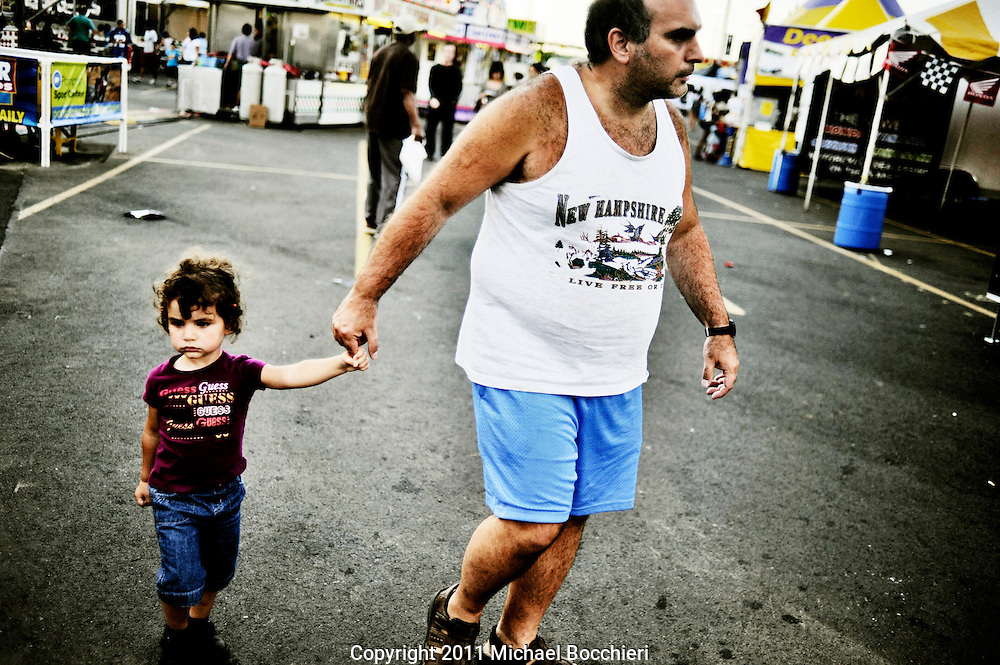 EAST RUTHERFORD, NJ - July 01:  A man holds a childs hand at the State Fair at the New Meadowlands Fairgrounds on July 01, 2011 in EAST RUTHERFORD, NJ.  The first Fair at the Meadowlands opened in 1986 as a 6-day event encompassing 10 acres offering a dozen rides and games. Today State Fair Meadowlands at Giants Stadium Fairgrounds is the largest in New Jersey and in the NY Metro area encompassing 35 acres, featuring over 150 rides and attractions plus over 75 food vendors from around the country.  (Photo by Michael Bocchieri/Bocchieri Archive)