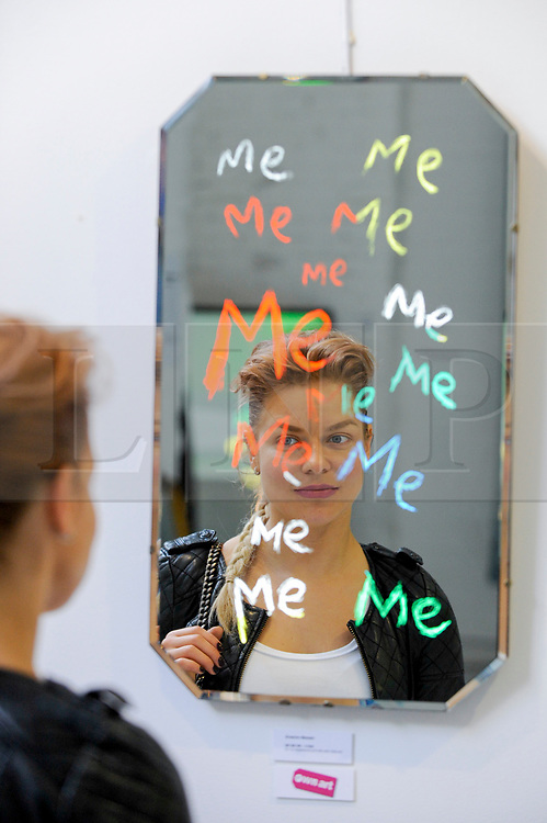 "© Licensed to London News Pictures. 31/03/2017. London, UK.  A visitor views ""Me, Me, Me"", one in the series of ""Will I Ever Make It"" mirror works by Graham Messer Opening day of The Other Art Fair, presented by Saatchi Art, which runs until 2 April in Bloomsbury.  The fair is collection of artworks by 120 emerging artists selected by a committer of art experts including Lulu Guinness OBE, Kate Bryan, Head of Collections at Soho House Group, and Rebecca Wilson, Chief Curator of Saatchi Art. Photo credit : Stephen Chung/LNP"