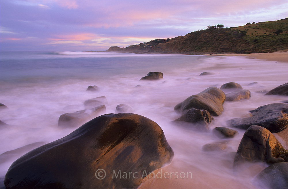 Rocky shore and misty sea at dusk, North Era Beach, Royal National Park, Australia.