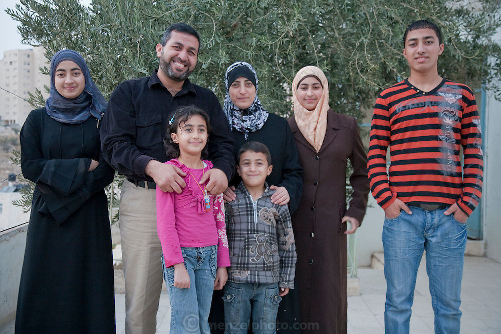 Abdul-Baset Razem, a Palestinian guide and driver, with his family in his backyard olive orchard in a Palestinean village in East Jerusalem.  (Abdul-Baset Razem is featured in the book What I Eat: Around the World in 80 Diets.)