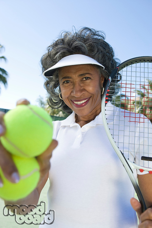 Senior woman holding tennis racket and balls, portrait