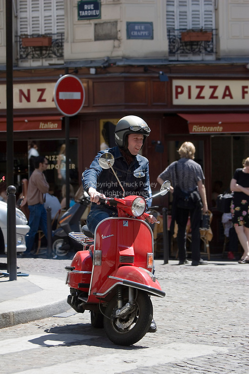 Man on red Vespa on Rue des Trois Freres, Monmartre, Paris France<br />